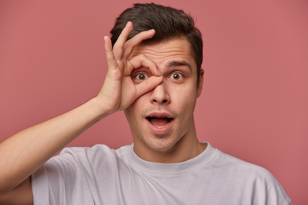 Indoor close-up of attractive brown eyed man with dark hair looking to camera with surprised face, keeping ok gesture next to eye, making fun over pink background in grey t-shirt