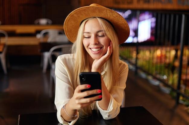 Primo piano dell'interno della giovane femmina bionda affascinante in camicia bianca e cappello marrone che si siede sopra l'interno del caffè, tenendo il cellulare in mano e guardando lo schermo con un sorriso allegro