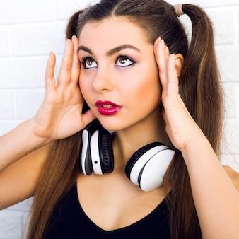 Ritratto di moda da vicino dell'interno di giovane bella donna, con trucco e acconciatura alla moda brillante, musica d'ascolto in auricolari, ritratto urbano luminoso di ragazza sexy dj