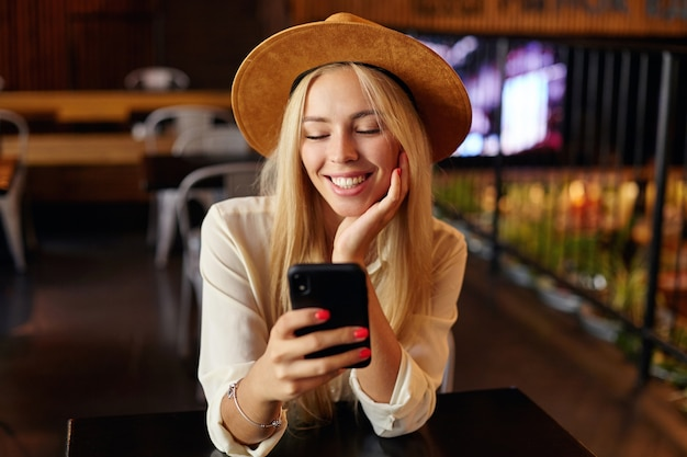 Крупный план очаровательной молодой блондинки в белой рубашке и коричневой шляпе, сидящей над интерьером кафе, держащей в руке мобильный телефон и смотрящей на экран с веселой улыбкой