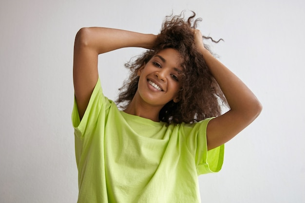 手で髪を保ち、魅力的な笑顔で見て、黄色のtシャツを着ているポジティブな暗い肌の若い女性の屋内クローズアップ