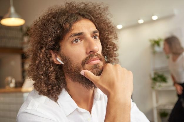 あごを持って、思慮深く自分の前を見て、ヘッドフォンと白いシャツを着て、カフェのインテリアの上でポーズをとって、真面目なひげを生やしたハンサムな男の屋内クローズアップ
