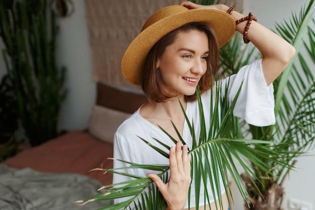 麦わら帽子と白いブラウスを自宅でポーズでエレガントなきれいな女性の肖像画間近で屋内