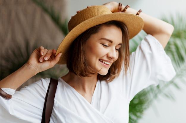 麦わら帽子と白いドレスが自宅でポーズでエレガントなきれいな女性の肖像画間近で屋内