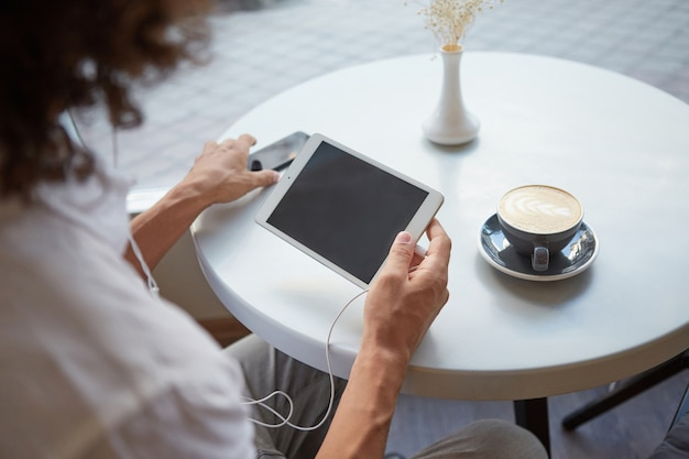 Indoor close-up side view of man's hands over cafe table, holding tablet with earphones, reaching for smartphone, going to have cup of coffee