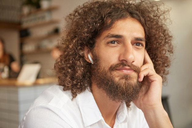 あごひげと茶色の目を持つ格好良い若い男性と、カフェに座って音楽を聴き、頬に寄りかかって、思慮深く窓を眺めている屋内のクローズアップ