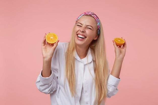 Primo piano dell'interno con bella giovane femmina bionda che ride con gli occhi chiusi e che tiene arancio tagliato nelle sue mani, in piedi