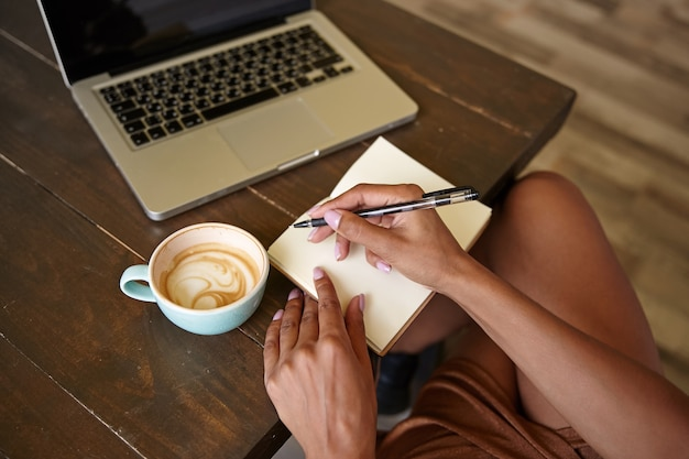Indoor close-up of wooden countertop with laptop on it, freelancer female working in public place with her notebooks and drinking coffee