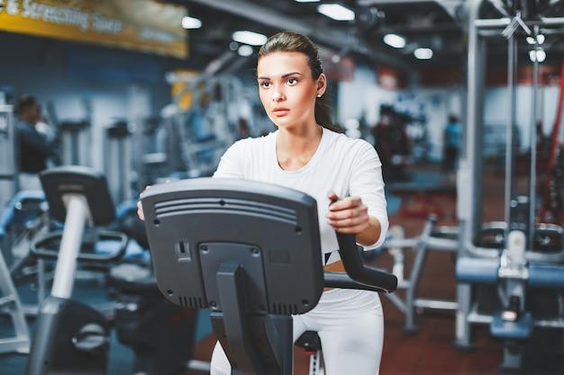 屋内ジム自転車で有酸素運動自転車をやっている屋内サイクリング女性。