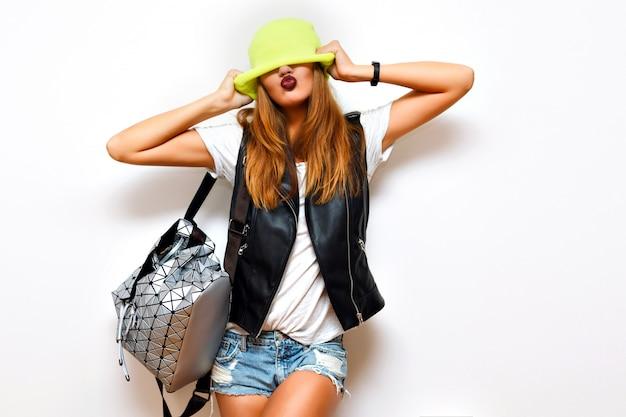 生意気な流行に敏感な女性、レザージャケット、ロックスタイル、暗い唇、フラッシュ、クレイジーな感情の屋内ファッショングランジの肖像画。彼女の目に帽子をかぶってください。