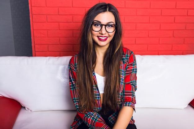明るいメイクと素晴らしい笑顔でかなり流行に敏感な若い女の子の屋内ファッションライフスタイルの肖像画は、長いブルネットの髪、格子縞のシャツを着ています。