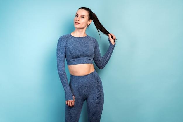젊은 백인 갈색 머리 여자의 실내 패션 초상화. 섹시 캐주얼 블루 스포츠 의상을 입고 소녀입니다. 손으로 머리를 잡고. 스포츠우먼 컨셉