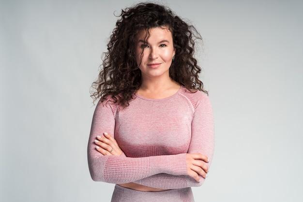 팔짱을 끼고 포즈를 취하는 섹시한 캐주얼 핑크색 스포츠 복장을 한 백인 갈색 곱슬머리 여성의 실내 패션 초상화. 그녀는 흰색 배경에 고립 미소