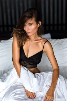 Ritratto di moda al coperto di donna bruna sexy che indossa reggiseno di pizzo nero e rilassarsi nel suo cattivo stile di vita di lusso, bellezza naturale, tempo del mattino.