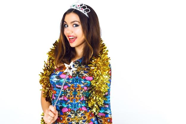 Крытый модный студийный портрет красивой улыбающейся молодой тусовщицы в ярком сексуальном коктейльном платье
