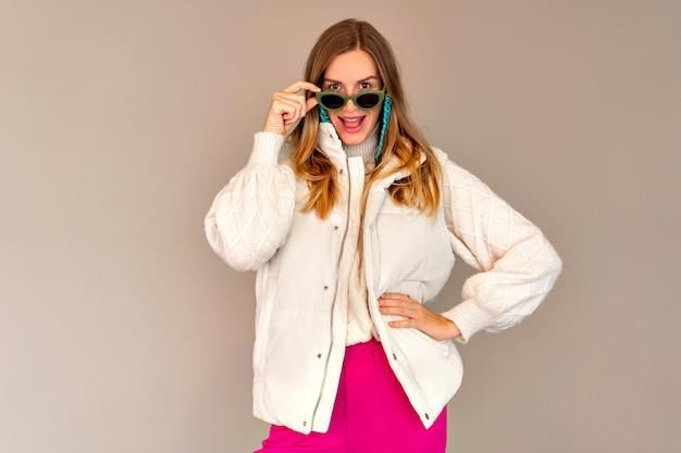 Крытый модный портрет довольно стильной женщины в вязаном свитере и белом теплом жилете