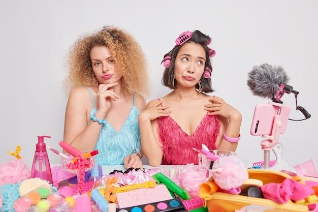 실내 여성 블로거는 미용 제품으로 둘러싸인 축제 의상을 입고 데이트 준비를 하고 구독자와 라이브 스트림 비디오 토크를 하고 소셜 미디어에서 팟캐스트 리뷰를 합니다. 인플루언서 마케팅