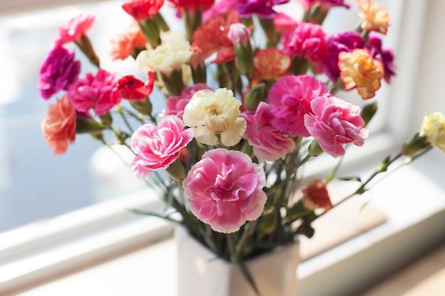 창턱에 실내 꽃입니다. 흰색 꽃병, 냄비. 커튼, 얇은 명주 그물