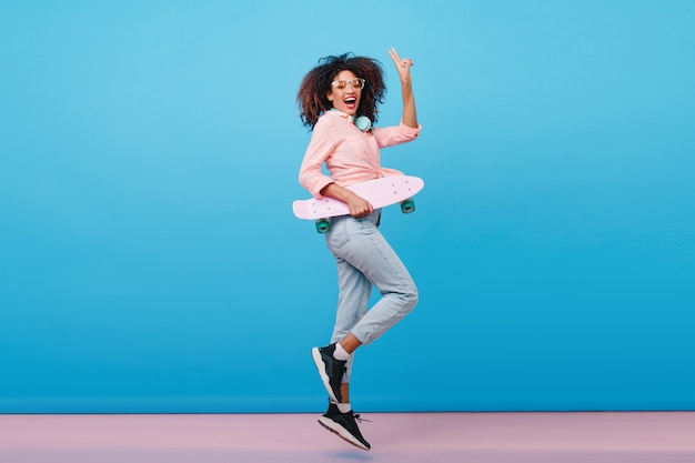 Indoor full-length portrait of confident african girl in pink shirt holding skateboard. enthusiastic black woman with curly hairstyle posing with blue interior.
