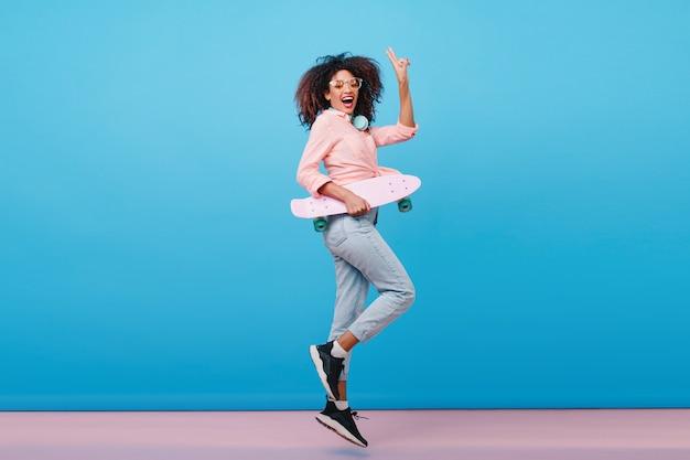 Крытый полнометражный портрет уверенно африканской девушки в розовой рубашке, держащей скейтборд. восторженная черная женщина с вьющейся прической позирует с синим интерьером.