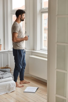 Indoor full length shot of thoughtful unshaven man in casual t shirt and trousers, stands near window, drinks coffee