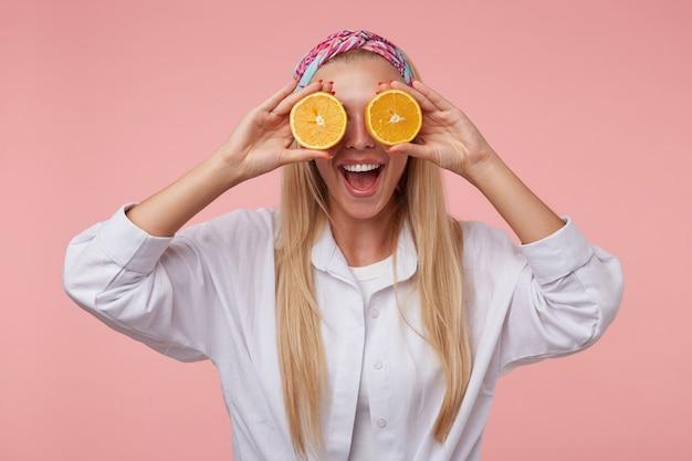 긴 금발 머리를 가진 예쁜 여성의 실내 재미있는 샷, 오렌지 반쪽으로 속이고 캐주얼 한 옷을 입고 포즈를 취하는