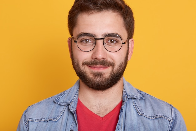 Indoor horizontal image of delighted good looking young man looking directly  smiling sincerely, wearing spectacles