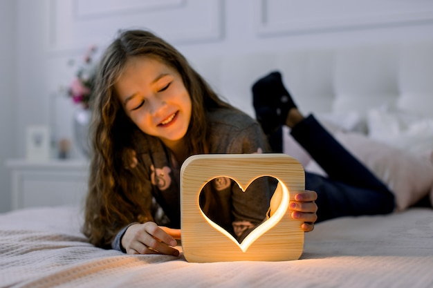 Indoor horizontal shot of beautiful child school girl, lying on the bed at home and having fun with stylish hand made wooden night lamp with heart picture.