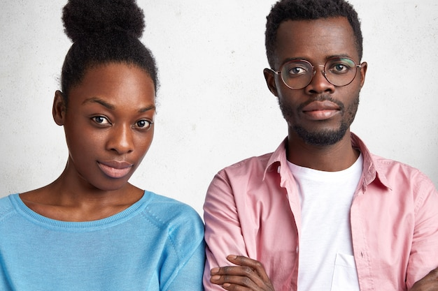 Indoor horizontal shot of confident attractive african american male and female looks with serious expression at camera, meet together to discuss future plans