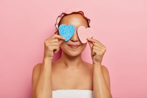 Indoor horizontal shot of delighted young asian woman covers eyes with two heart shaped sponges, has fun after taking shower, uses cosmetic products for applying cream, has dark smooth skin.
