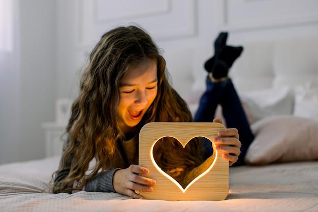 Крытый горизонтальный снимок красивой детской школьницы, лежащей на кровати дома и веселящейся со стильной деревянной ночной лампой ручной работы с изображением сердца.
