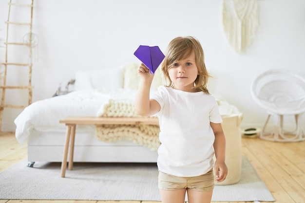 L'immagine dell'interno dell'affascinante bambina europea in abiti casual sta giocando al chiuso, tenendo con l'aereo di carta viola. bambini, divertimento, giochi, attività e tempo libero