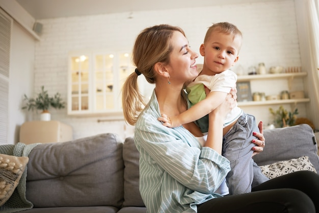Indoor image of cute young female with ponytail holding tight her charming baby, sitting on sofa with him. pretty mother and son bonding in living room, mom looking at child with love and tenderness