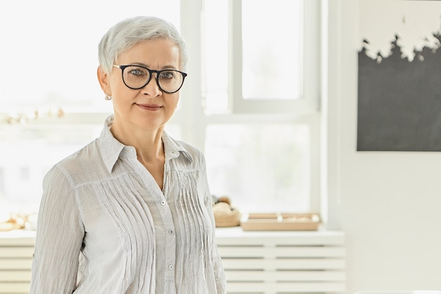 Indoor image of fashionable elegant mature european woman with short gray pixie haircut  with happy smile posing