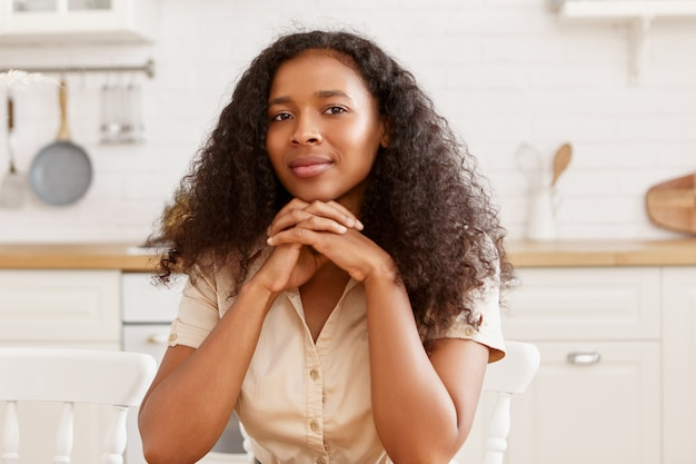 Indoor image of gorgeous young black dark skinned woman with afro hairstyle and tanned bronzed skin cooking in kitchen, sitting at table, keeping hands clasped under her chin, looking