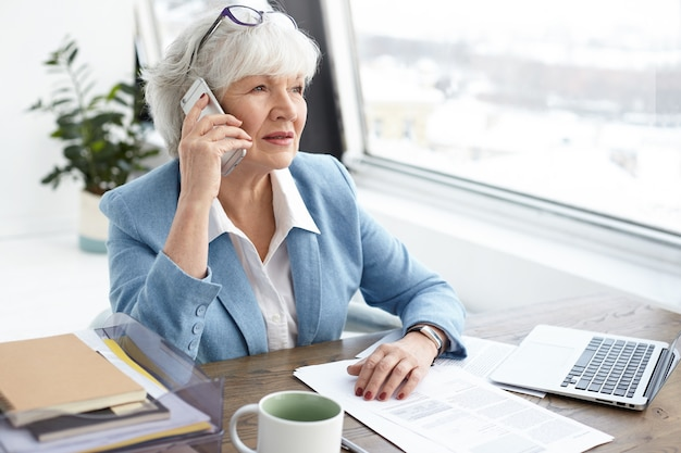 Indoor image of gray haired sixty year old mature female banker working in stylish office, discussing details of civil case with her client on mobile phone, sitting at desk by window, using laptop