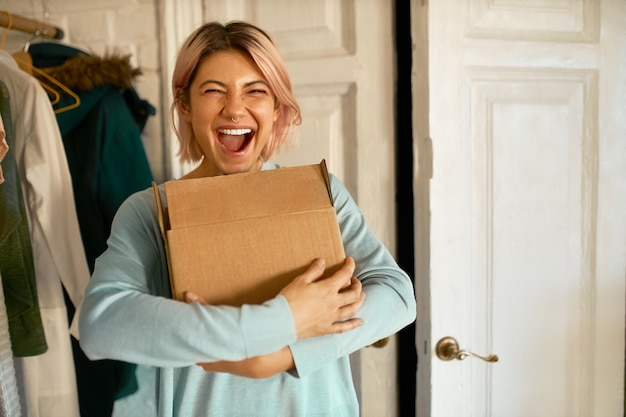 Indoor image of happy cheerful young woman holding cardboard box delivered to her apartment, expressing excitement, going to unpack parcel