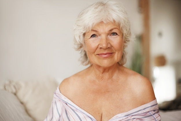 회색 머리와 깔끔한 매력적인 노인 백인 여자의 실내 이미지는 스트라이프 나이트 가운을 입은 침대에 앉아 어깨를 벗은 채로, 유혹적인 매혹적인 표정을 가지고 웃고