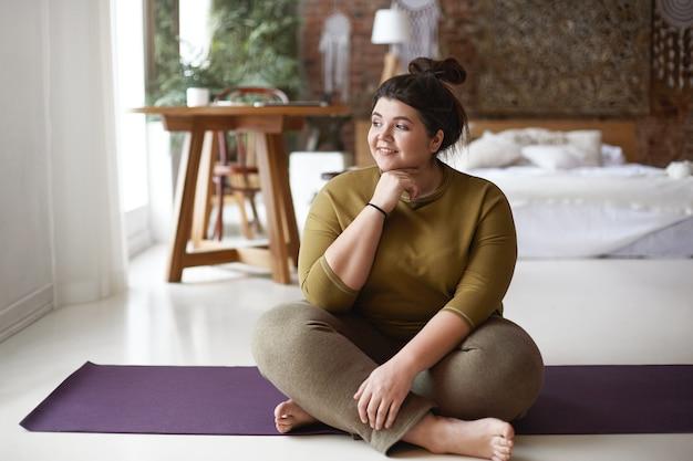 床でリラックスし、体育の後にヨガマットに座って、楽しい表情をしているスポーツウェアの魅力的なポジティブな太りすぎの若い白人女性の屋内画像。目をそらす