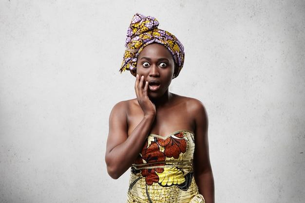 うっとりするような表情の伝統的な服を着ている浅黒い肌のアフリカ女性の屋内イメージ。虫眼鏡の目と白で隔離の頬に手を握って開いた口で見て驚いたの黒人女性