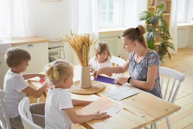広々としたリビングルームのダイニングテーブルに座って、子供たちに折り紙の作り方を教える若い女性のベビーシッターの屋内画像。家で母親と一緒に紙飛行機を作る3人の子供。