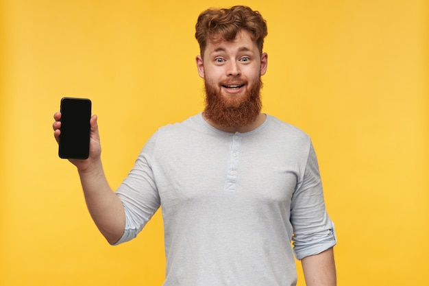 大きなあごひげを生やした若い男の屋内画像は、広く笑顔で、黄色の空白の黒いコピースペースで彼の携帯電話のディスプレイを示しています