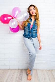 パーティーの準備ができて、ピンクの風船で遊ぶ若いトレンディな流行に敏感な金髪女性の屋内イメージ。