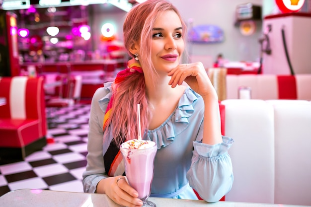 Indoor image of pretty young elegant woman enjoying her tasty sweet strawberry milk shake at retro vintage american restaurant, neon design, cute pastel dress, pink hairs and accessories