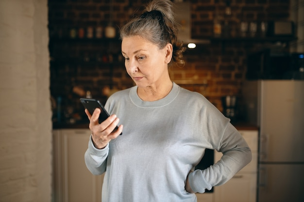 Indoor image of serious gray haired female pensioner in casual clothes spending days at home because of social distancing, reading world news while surfing internet on mobile phone using wifi