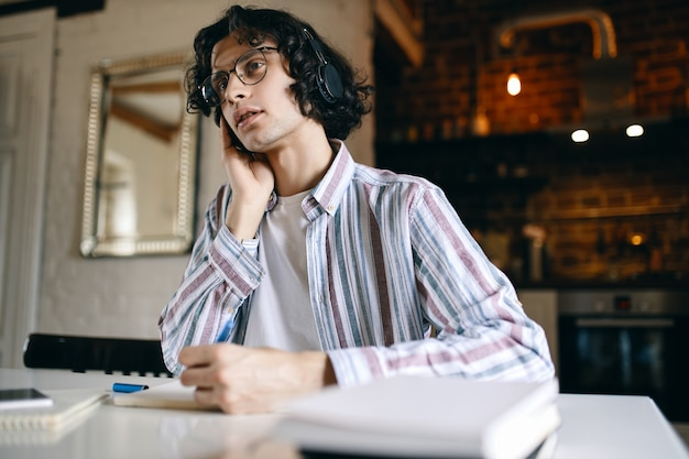 Indoor image of serious young male with curly hair sitting at his workplace with textbooks, writing down while listening to lecture via wireless headphones, learning from home. social distancing