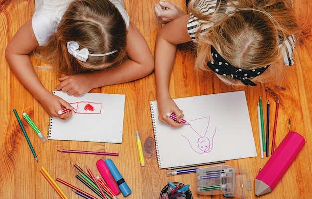 Indoor leisure activity. two girls drawing lying on the floor.