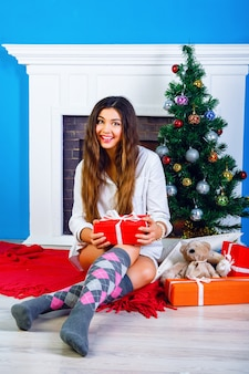 Indoor lifestyle bright portrait of happy pretty young girl sitting at home her christmas tree, wearing pajama. opening new year presents and having fun near fireplace.