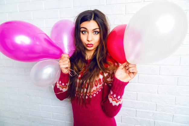 Indoor lifestyle image of funny pretty brunette girl with bright makeup and long hairs, wearing trendy sweater and holding pink party balloons.