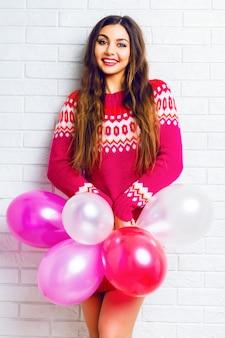 明るいメイクと長い髪、トレンディなセーターを着て、ピンクのパーティーバルーンを保持している面白いかなりブルネットの少女の屋内ライフスタイルイメージ。
